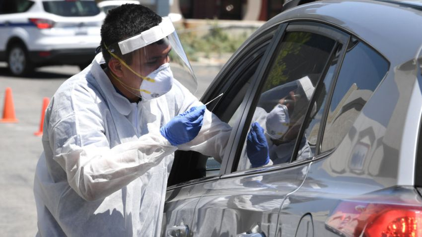 A worker wearing personal protective equipment (PPE) performs COVID-19 test on driver in car