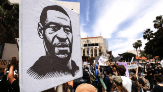 A protester holds a sign with an image of George Floyd during a peaceful demonstration over Floyd's death outside LAPD headquarters on June 2, 2020 in Los Angeles, California.