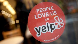In this March 1, 2012, file photo, the Yelp Inc. logo is displayed in the window of a restaurant in New York.