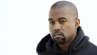 In this March 6, 2015, file photo, Kanye West poses before Christian Dior 2015-2016 fall/winter ready-to-wear collection fashion show in Paris.