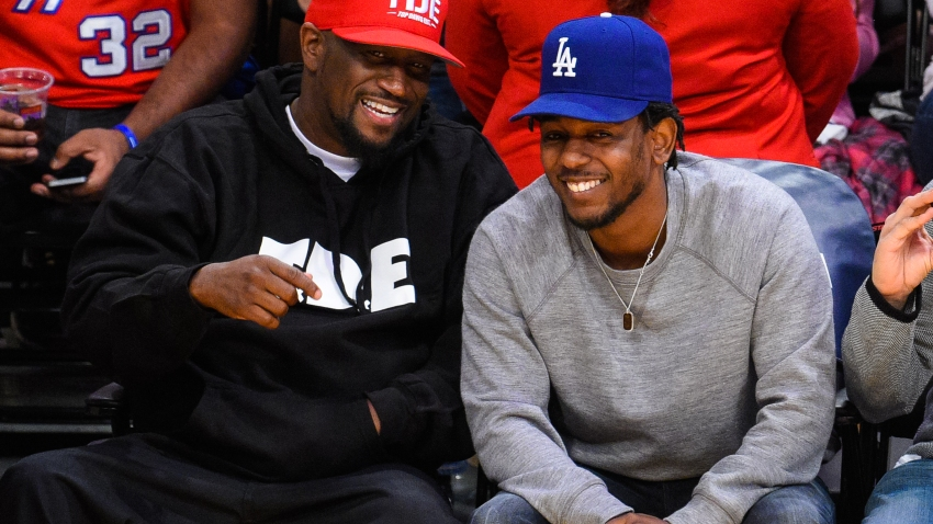 Anthony Tiffith, left, and Kendrick Lamar sit courtside at a basketball game between the Los Angeles Clippers and the Los Angeles Lakers at Staples Center on April 5, 2015.