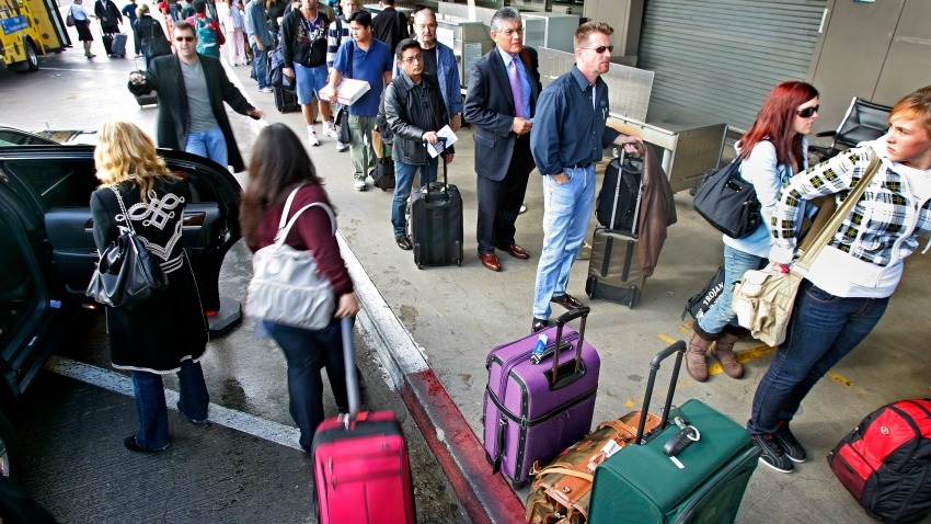 Thanksgiving travelers wait in the security line at Terminal 1 at LAX