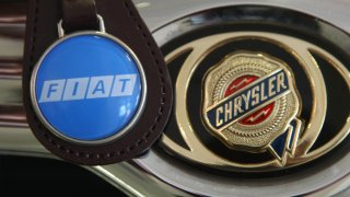 A Fiat logo on a keychain dangles next to the hood ornament of a Chrysler car