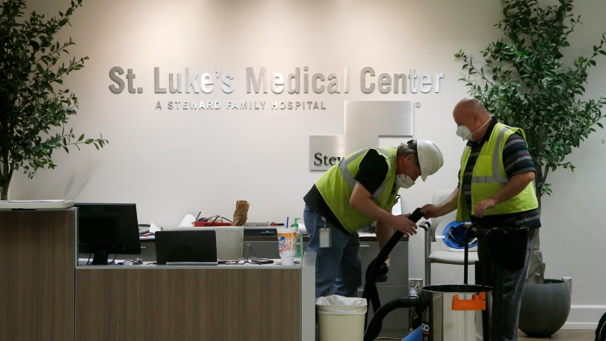 In this April 23, 2020, file photo, contract workers join the Army Corps of Engineers as they get the currently dormant St. Luke's Hospital ready for reopening in the case of a surge of coronavirus patients in Phoenix.