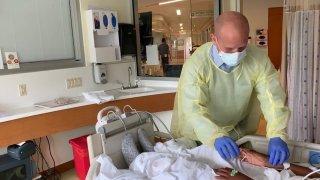 Dr. James Schneider checks pulse of a patient