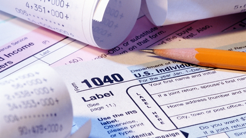 A stock photo shows income tax forms, receipts and a sharpened pencil.