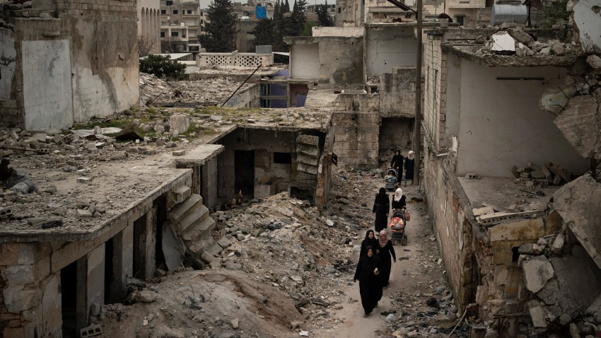 In this Thursday, March 12, 2020 photo, women walk in a neighborhood heavily damaged by airstrikes in Idlib, Syria.
