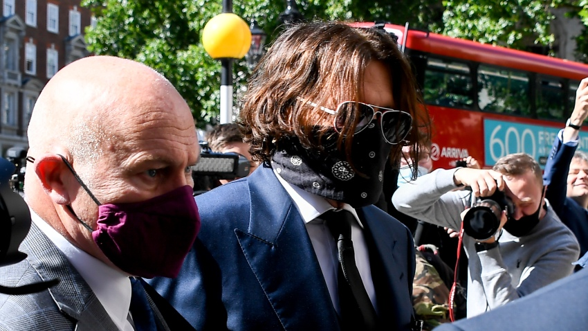 "Johnny Depp, right, wearing a protective mask arrives at the Royal Court of Justice, in London, Tuesday, July 7, 2020. Johnny Depp is suing a tabloid newspaper for libel over an article that branded him a ""wife beater."""
