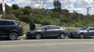 meter maid giving tickets to cars along road