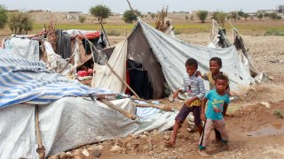 Yemeni children play next to tents damaged by torrential rain in a makeshift camp for the displaced in the northern Hajjah province, on April 19, 2020.