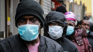 In this April 18, 2020, file photo, people wait for masks and food from the Rev. Al Sharpton in the Harlem neighborhood of New York, after a new state mandate was issued requiring residents to wear face coverings in public due to COVID-19.