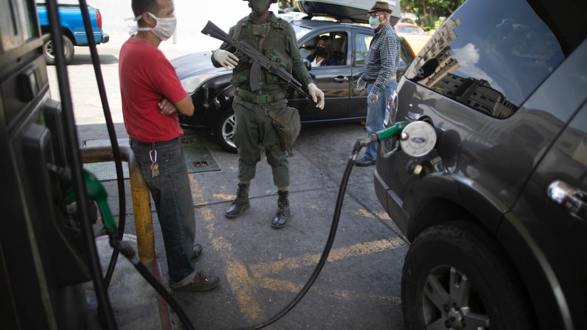A soldier stand guard as a customer wearing a protective face mask fills up his gas tank, amid a nationwide quarantine to slow the spread of the new coronavirus, in Caracas, Venezuela, Tuesday, April 7, 2020.