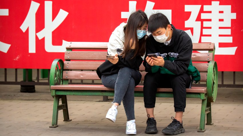 People wearing face masks to protect against the spread of the new coronavirus sit on a bench in front of a propaganda banner encouraging people to wear masks at a public park in Beijing, Thursday, May 7, 2020.