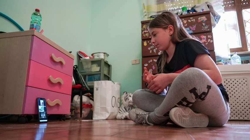 In May 14, 2020, file photo, Elena Moretti looks at her cellphone as she prepares to attend an online dancing lesson, in her bedroom in Rome. For the 11-year-old, the COVID-19 coronavirus pandemic is not some faraway threat: Italy was the first European country to be hit by COVID-19, and her mother is a doctor in the public health system that has seen 25,000 personnel infected and more than 160 doctors dead nationwide.