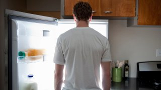 Man standing looking at contents of fridge