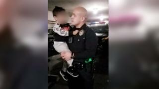 Armando Corona, in police uniform, holds one of his kids