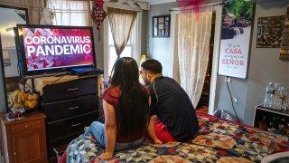 La inmigrante indocumentada Juana, de 24 años, y su esposo Saul, de 23, miran noticias locales en su apartamento de una habitación. Juana perdió su trabajo como limpiadora de casas y Saul como pintor debido a la pandemia del coronavirus.
