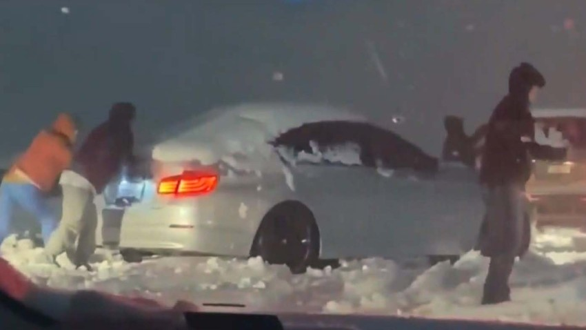 Drivers push car stuck in snow on freeway