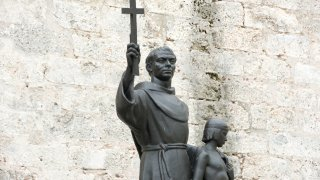 Statue of Junipero Serra holding a cross and the shoulder of an indigenous boy