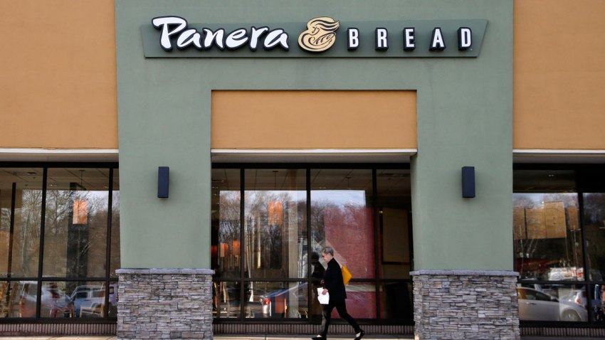 In this Wednesday, April 12, 2017, file photo, a passer-by walks near an entrance to a Panera Bread restaurant in Natick, Mass.