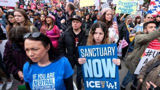 """In this Feb. 18, 2017, file photo, thousands of people take part in the """"Free the People Immigration March,"""" to protest actions taken by President Donald Trump and his administration, in Los Angeles. A federal appeals court has given the Trump administration a rare legal win in its efforts to crack down on sanctuary cities."""