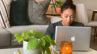 A woman works from home with a laptop computer.