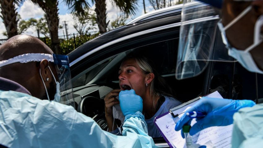 "A medical personnel member takes samples on a woman at a ""drive-thru"" coronavirus testing lab set up by a local community center in West Palm Beach"