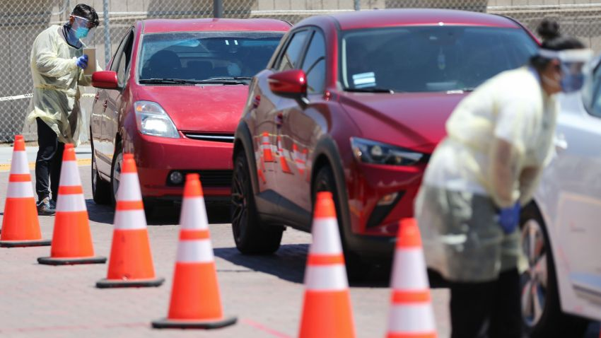 In this July 31, 2020, file photo, vehicles line up at a drive-in COVID-19 testing center at Charles R. Drew University of Medicine and Science in South Los Angeles amid the coronavirus pandemic in Los Angeles, California.