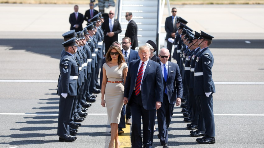 U.S. President Donald Trump, center, U.S. First Lady Melania Trump, left, and Woody Johnson, U.S. ambassadorto the United Kingdom, make their way to Marine One after arriving nat London Stansted Airport in Stansted, U.K., on Thursday, July 12, 2018. Trumpwill avoid London as much as possible as he's whisked off on a tour of prime British real estate to keep him away from protesters during his U.K. visit.