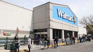 Las personas que usan máscaras y guantes esperan para ingresar a Walmart el 17 de abril de 2020 en Uniondale, Nueva York