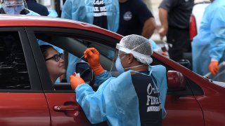 In this July 22, 2020, file photo, a woman in a car is tested for COVID-19 at a drive-thru testing site at Camping World Stadium in Orlando, Florida.