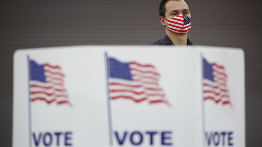 A poll worker wearing an American flag themed protective mask