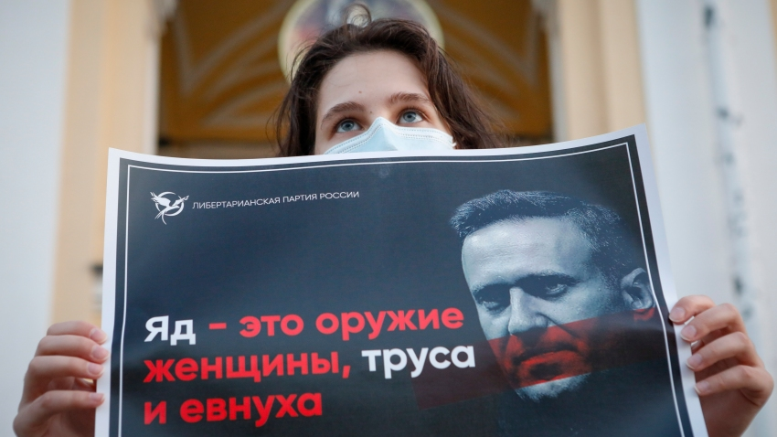 """A protester stands holds a poster reads """"poison is the weapon of a woman, a coward and a eunuch!"""" during a picket in support of Russian opposition leader Alexei Navalny in the center of St. Petersburg, Russia, Thursday, Aug. 20, 2020. Russian opposition politician Alexei Navalny is on a hospital ventilator in a coma, after falling ill from a suspected poisoning, according to his spokeswoman Kira Yarmysh."""