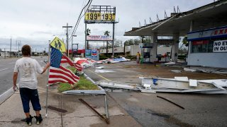 Dustin Amos walks near debris at a gas station on Thursday, Aug. 27, 2020, in Lake Charles, La., after Hurricane Laura moved through the state.