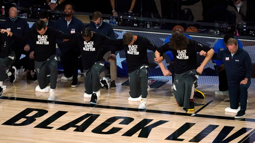 Members of the Milwaukee Bucks join arms as they kneel during the national anthem before an NBA basketball first round playoff game against the Orlando Magic Saturday, Aug. 29, 2020, in Lake Buena Vista, Fla.