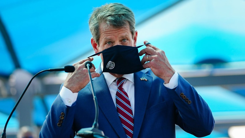 Georgia Gov. Brian Kemp puts on a mask after speaking at a press conference announcing statewide expanded COVID testing, Aug. 10, 2020, in Atlanta.