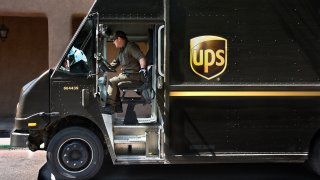 A UPS driver sits in a UPS big brown truck