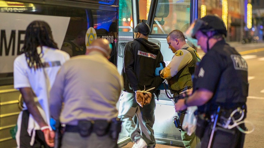 Arrestees are loaded onto a sheriff's bus to be taken to jail as large numbers of people are arrested after a curfew went into effect during demonstrations over the death of George Floyd.