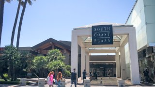 Shoppers enter South Coast Plaza Monday, which will be closed down Tuesday for a second time by Gov. Newsom in an attempt to slow the spread of coronavirus on Monday, July 13, 2020 in Costa Mesa, CA.