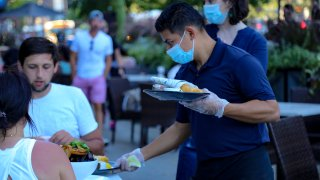 A waiter wearing a protective mask serves food to patrons