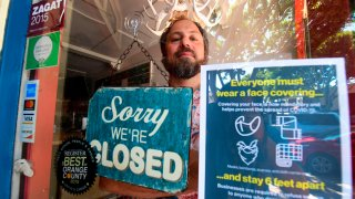 In this July 28, 2020, file photo, Gabriel Gordon stands behind the glass entrance door to his restaurant Beachwood BBQ, open for 14 years in Seal Beach, California, but closing soon due to the economic situation around the coronavirus pandemic.