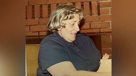 Woman with a blue shirt sits looking down