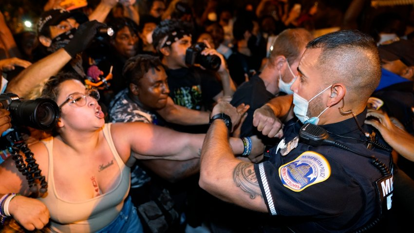 Metropolitan Police are confronted by protestors as police carry away a handcuffed protestor along a section of 16th Street, Northwest, renamed Black Lives Matter Plaza, Thursday night , Aug. 27, 2020, in Washington, after President Donald Trump had finished delivering his acceptance speech from the White House South Lawn.
