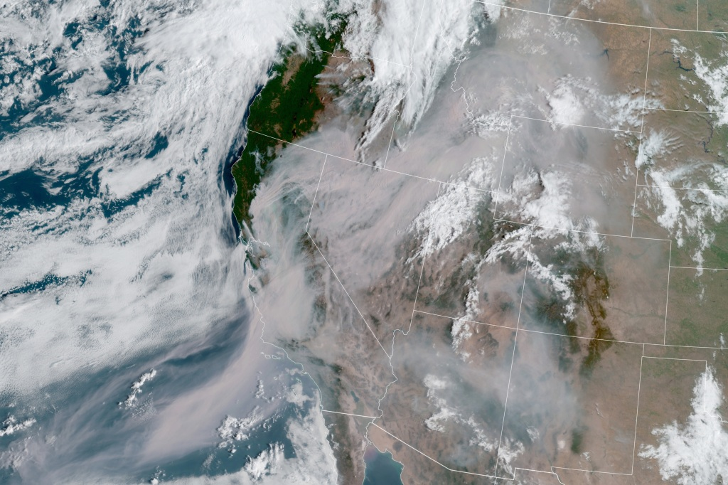 A satellite image captured Thursday shows smoke from those fires shrouding most of California and much of the U.S. West
