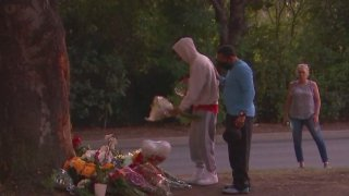 Mourners leave flowers at a memorial.