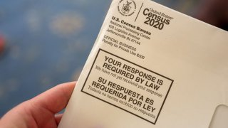 Close-up of human hand holding a letter from the Census Bureau