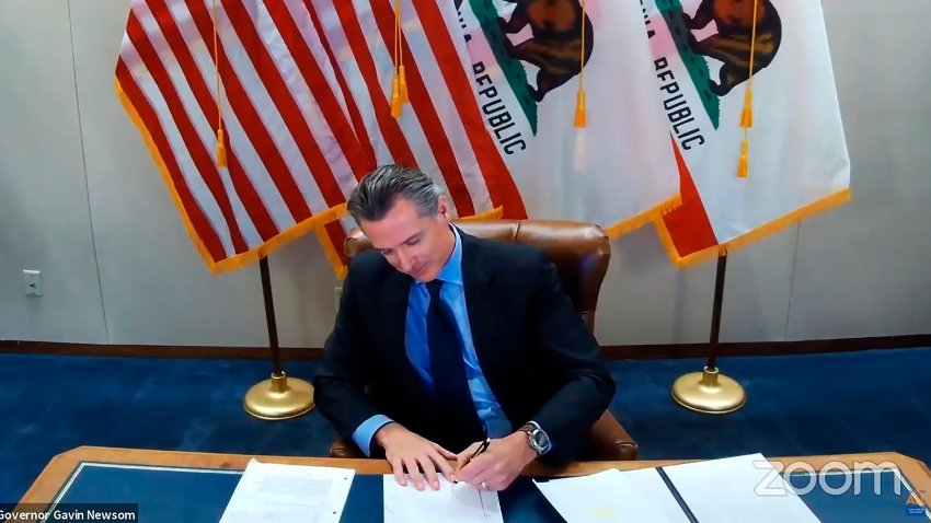 This image made from video from the Office of the Governor shows California Gov. Gavin Newsom signing into law a bill that establishes a task force to come up with recommendations on how to give reparations to Black Americans on Wednesday, Sept. 30, 2020, in Sacramento, Calif. The law establishes a nine-member task force to come up with a plan for how the state could give reparations to Black Americans, what form those reparations might take and who would be eligible to receive them.