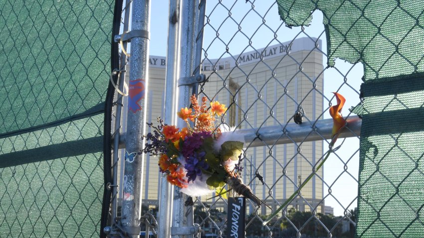 """Flowers and a sign reading """"HONOR 58"""" hang on a fence outside the Las Vegas Village across from Mandalay Bay Resort and Casino as a tribute to those killed almost two years ago in a massacre at the site on September 30, 2019 in Las Vegas, Nevada. On October 1, 2017, a gunman opened fire from the 32nd floor of Mandalay Bay on the Route 91 Harvest country music festival in Las Vegas killing 58 people and injuring more than 800 in the deadliest mass shooting event in U.S. history."""