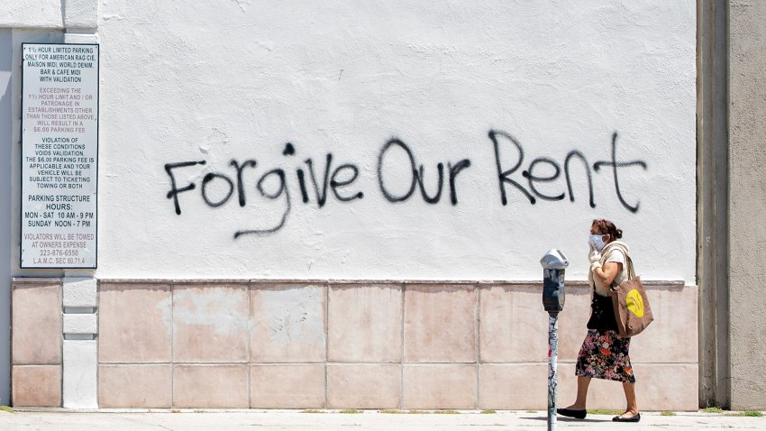 A woman wearing a mask walks past a wall bearing a graffiti asking for rent forgiveness on La Brea Ave.