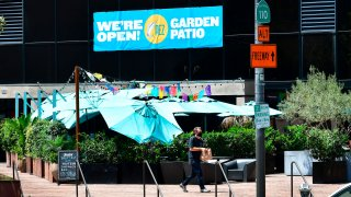 A man carries his takeout order past umbrellas covering an outdoor patio dining area in Los Angeles.
